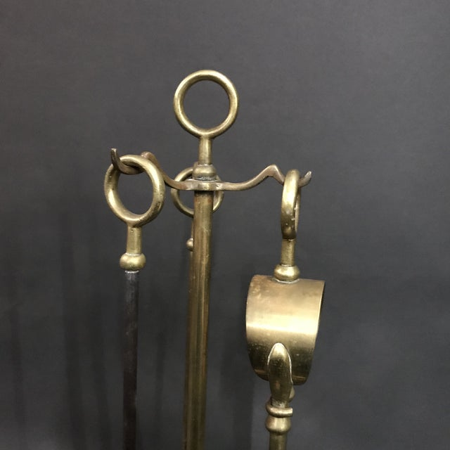 A 1950's compact set of three fireplace tools in cast iron and brass hung on a weighted base. Includes poker, tongs and...