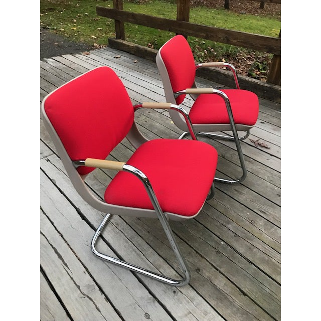 A pair of chrome and red fabric cantilever arm chairs with clay colored sculptural bodies.