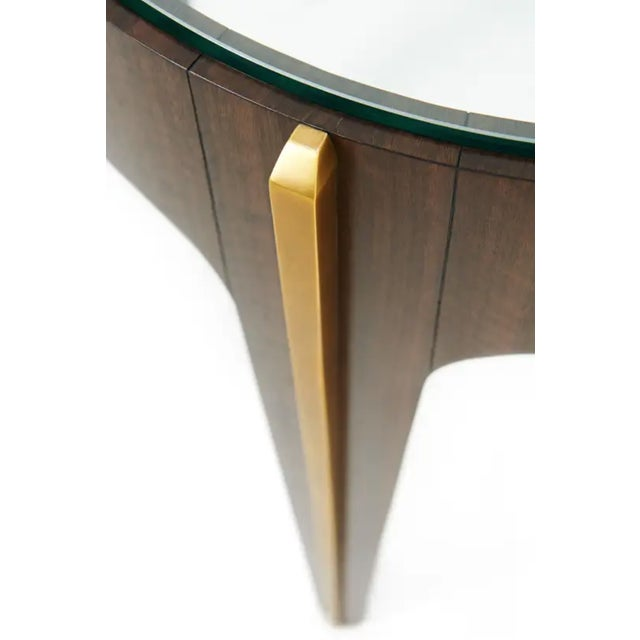 A fumed Eucalyptus veneered and brass mounted lamp table, the circular tempered glass inset top within a bold veneered...