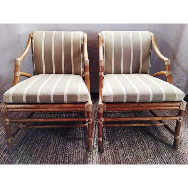 Stunning pair of vintage (1964) rattan accent chairs by McGuire Furniture. Chairs have cane seats and backs with silk seat...