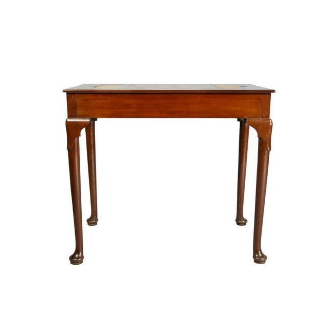 With rectangular top with reversible removable game board revealing a backgammon surface raised on slight cabriole legs...