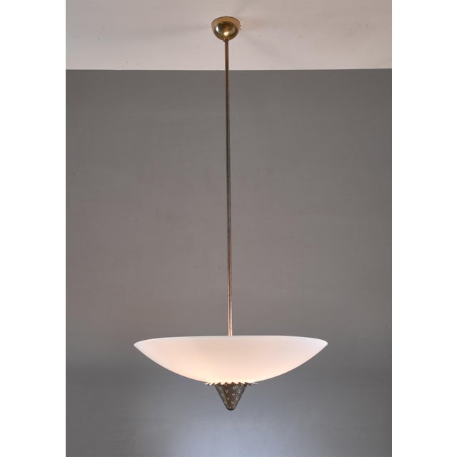 A model 1090 pendant lamp by Lisa Johansson-Pape for Orno, Finland. This 1950s pendant has an opaline glass shade with a...