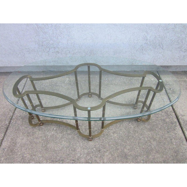 Bevelled oval shaped glass top with a brass, decorative faux bamboo base. Some scratches to the glass. The length below is...