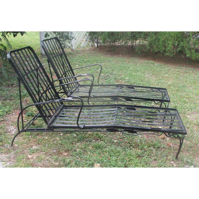 A Pair of mid-century modern Woodard outdoor chaise lounges in the maple leaf pattern. Painted black. Some of the paint...