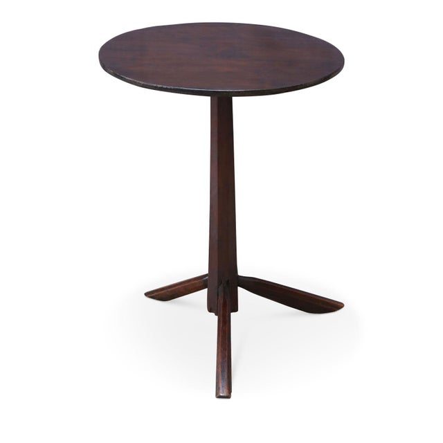 Unconventional vintage side table with a round top raised upon a tapered pedestal supported by an asymmetrical tripod...