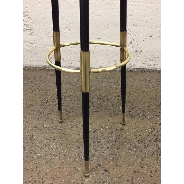 "The stool is metal with brass trim and a brown, soft leather seat. Measures: 32.5""H. Seat diameter is 10"""