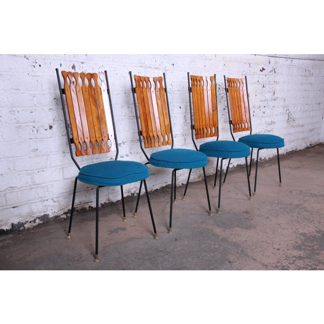Offering a rare and unique set of four mid-century modern iron, wood, and upholstered high back dining chairs designed by...