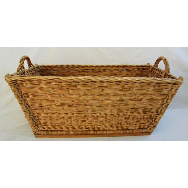 Early 1900s French handmade wicker and willow market basket with braided rim and handles and woven bottom and sides. No...