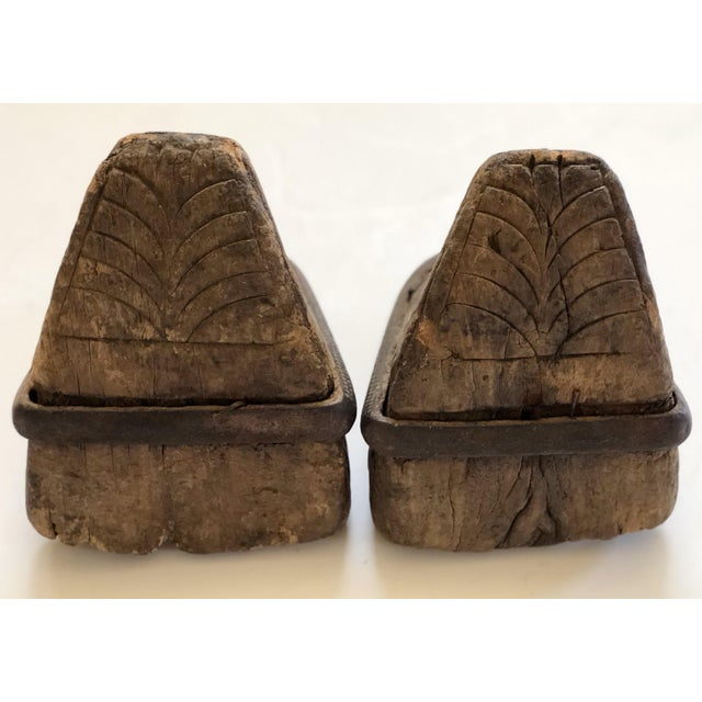 This pair of antique wooden stirrups is made of heavily carved wood on the top and sole with metal straps surrounding...