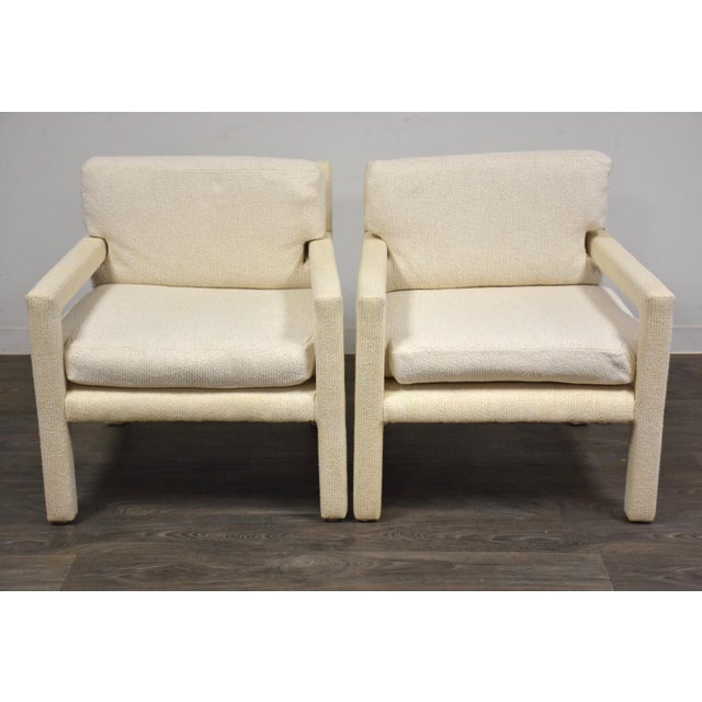 A pair of mid century modern off-white parsons lounge chairs designed by Milo Baughman for Thayer Coggin. Cushions are...