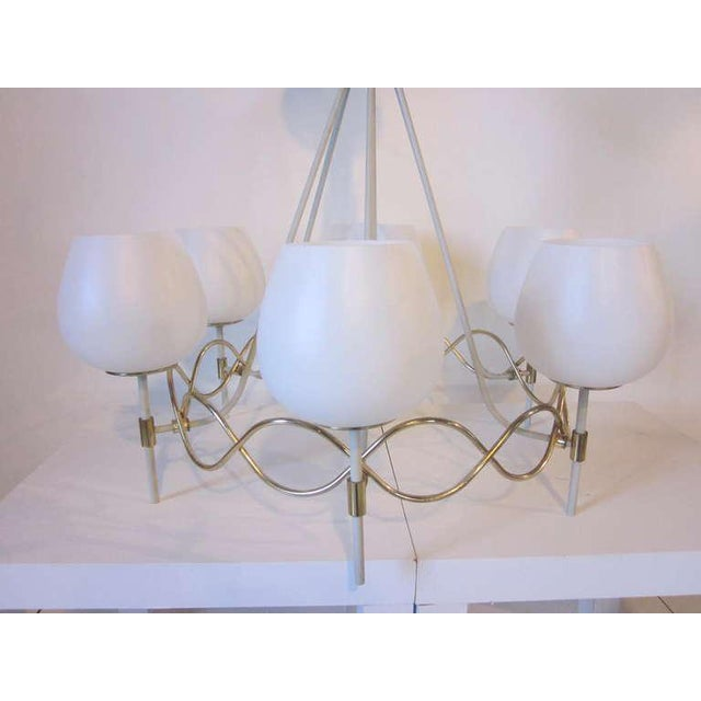 A Mid-Century chandelier with six white globes sitting on wave-like sinusoid- sphere brass metalwork with radiating...