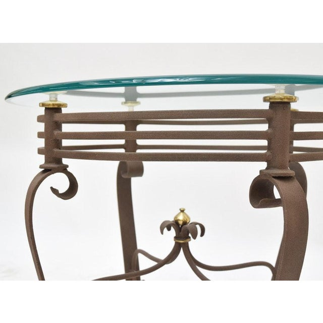 A French fer forge, country styled, Art Deco inspired, metal side table with a rust finish and brass tone accents. This...