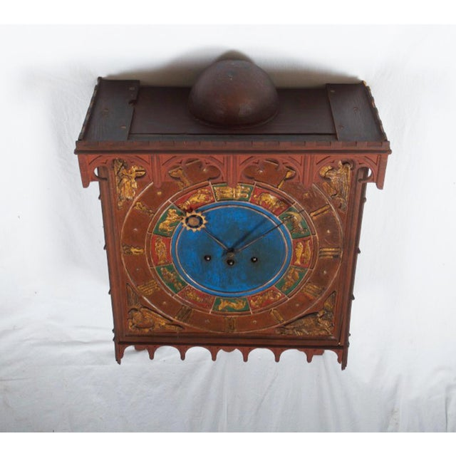 Wooden painted box with Gothic-style carvings, clock face with carvings in the form of a zodiac sign, supplied pendulum...