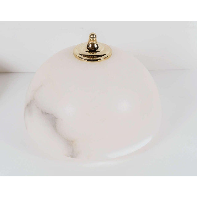 Sophisticated pair of Art Deco alabaster dome flush mounts with brass fittings tipped with a brass ball detail. The...