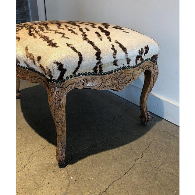 """Early 20th century hand-carved French ottoman upholstered in vintage Tiger velvet fabric. 30""""W x 24""""D x 18""""H."""