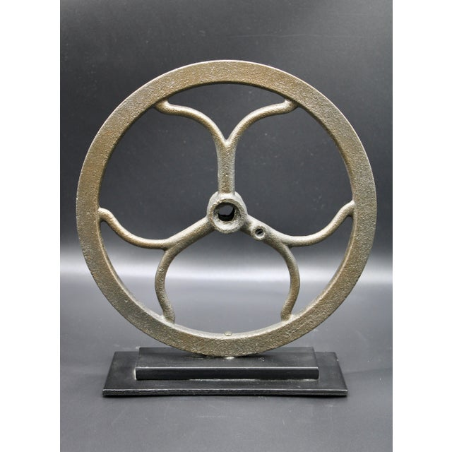 Vintage iron pulley wheel originally used to change the direction of an applied force by means of a center axle and...