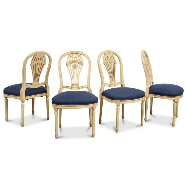 The cream painted set of 4 chairs with upholstered seats. No makers mark.