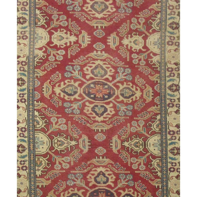 This beautiful rug is handmade, made in Iran. It features a pattern in a vibrant combination of red, ivory, blue, and...