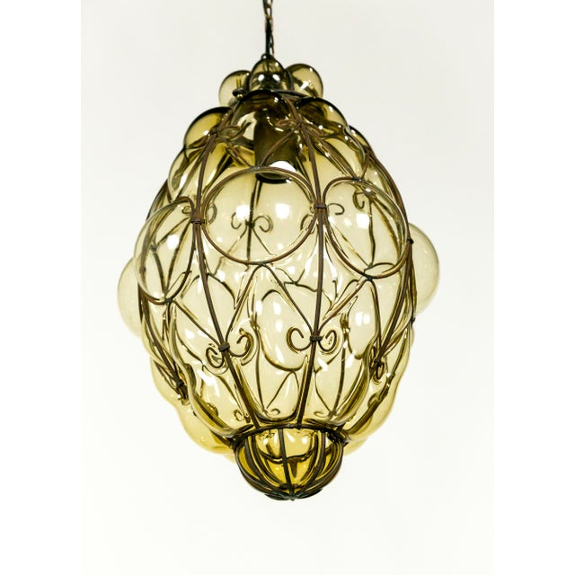 This fabulous 1940's pendant is made with amber glass, handblown into an iron wire armature. Its inviting appearance and...