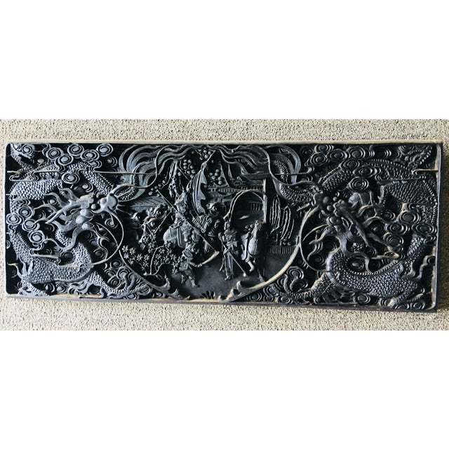 Created around 1900 this large black lacquer plaque shows two dragons and aI scene with military men. Highly detailed.