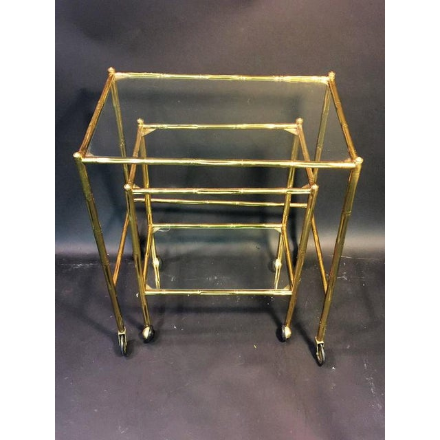 Quality pair of brass bamboo nesting tables designed by Baques fitted with two types of caster wheels. The smaller table...