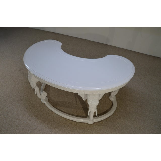 A beautiful Hollywood Regency kidney shaped writing desk having sculpted fretwork wooden elephant leg adornments by...