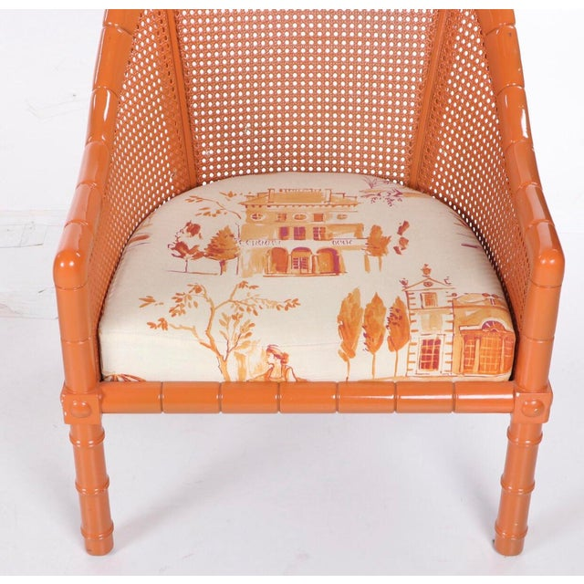 A pair of gorgeous orange lacquered vintage club/ lounge cane chairs with faux bamboo motif and newly upholstered seats in...