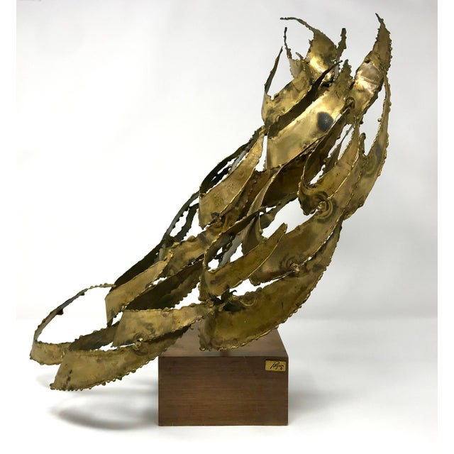 1960s brutalist patinated brass sculpture by Bijan J. Bijan. The sculpture is mounted on a wooden base, with Bijan's...