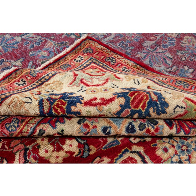 """An antique hand-knotted Persian Mahal rug with a red floral medallion motif. This rug measures at 9'5"""" X 12'8"""". Material:..."""