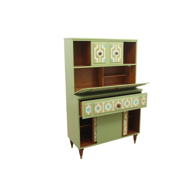 A mid century modern upright cabinet in green. Cabinet doors are finished with a newly applied mid century style fabric...