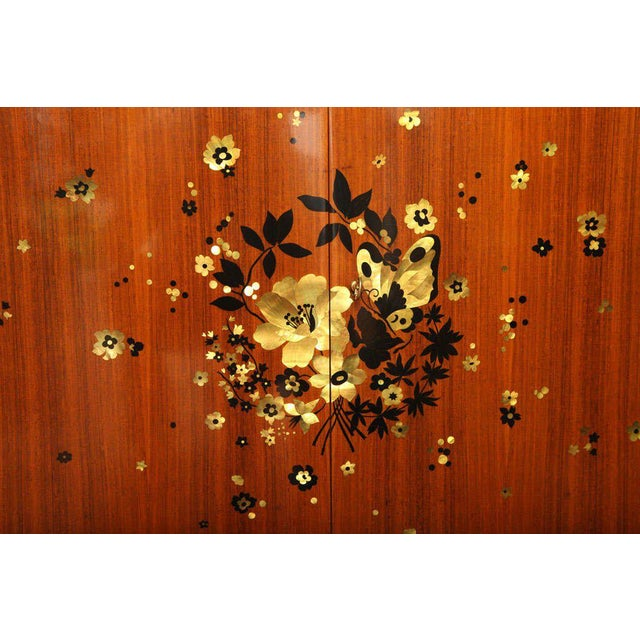 Jules Leleu (1883-1961). An important rosewood cabinet, decorated with a spray of inlay mother-of-pearl flowers and...
