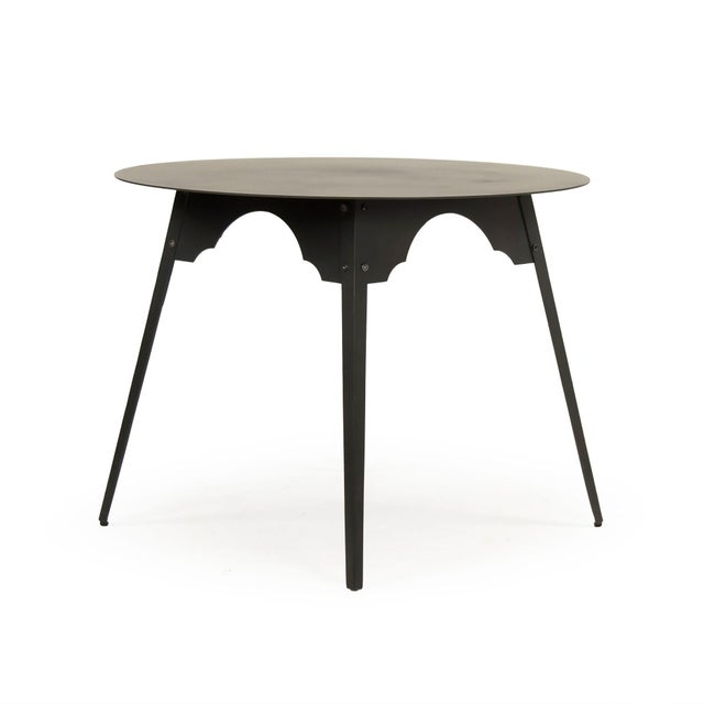 Circular metal table finished in antique black iron.