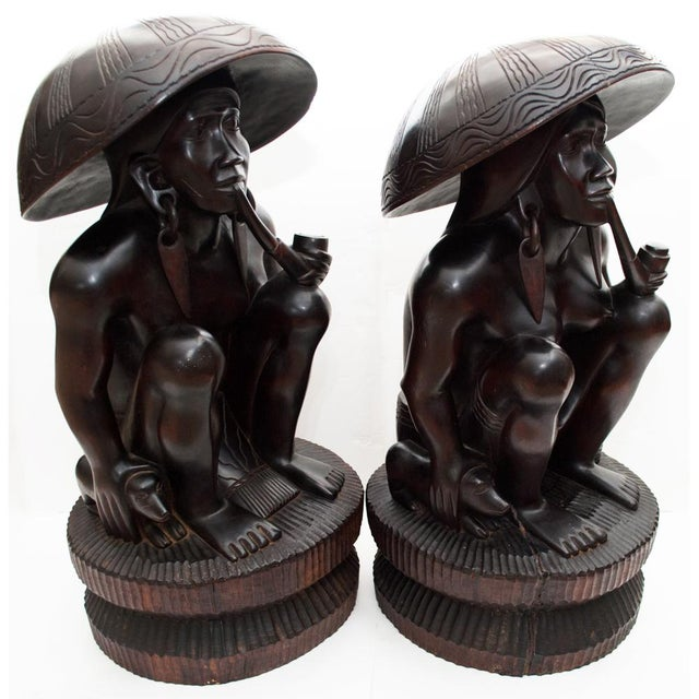 Exquisite rare and large pair of antique hand carved Narra wood statues of seated African man and woman on wood stands, in...