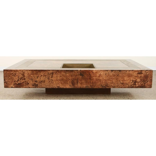 An Aldo Tura substantial goat skin coffee table having brass inlay and brass bottle insert.