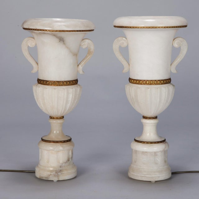 """Found in Italy, this pair of circa 1930s alabaster lamps stand just under 20"""" tall and feature a classic urn form with..."""