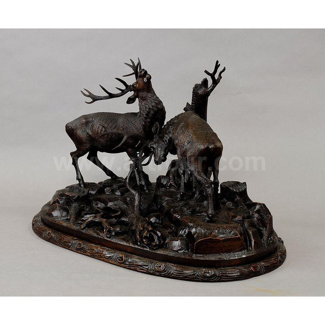 grandiose handcarved wood sculpture of fighting stags. very detailed natural carving by the austrian woodcarver rudolph...