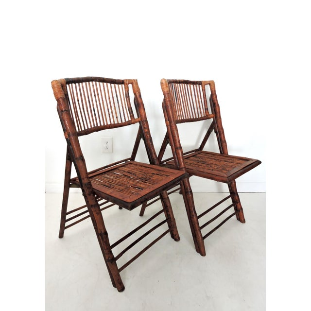 A pair of vintage burnt bamboo folding chairs - four pairs are available. The lacquered dining or side chairs feature...