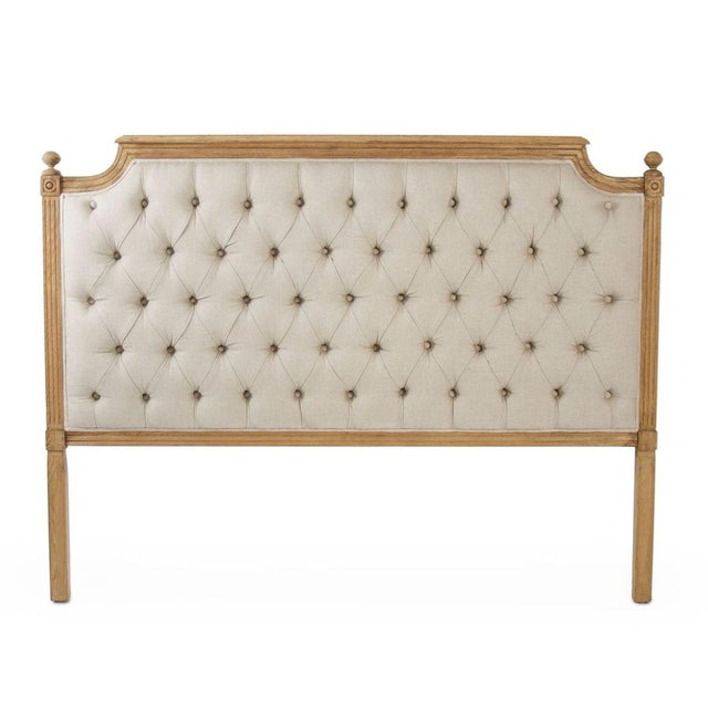 Tufted queen headboard upholstered in natural linen on natural oak.