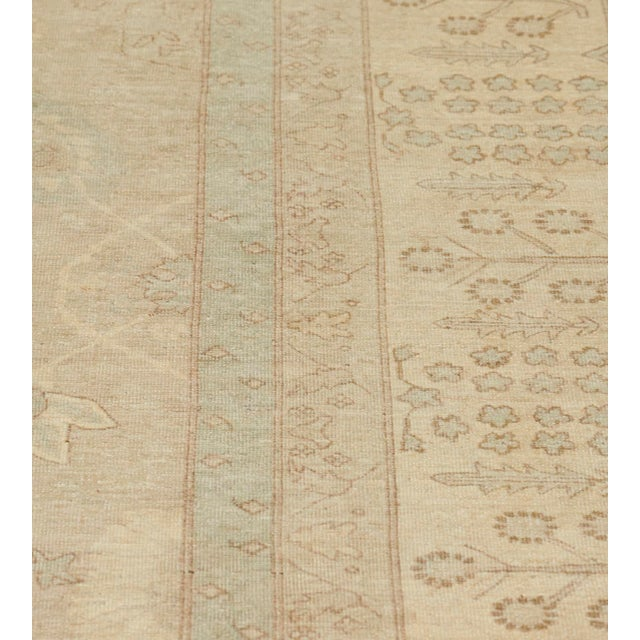This revival Tabriz rug has a sandy-taupe field with an overall design of light blue, chocolate-brown and ivory delicate...