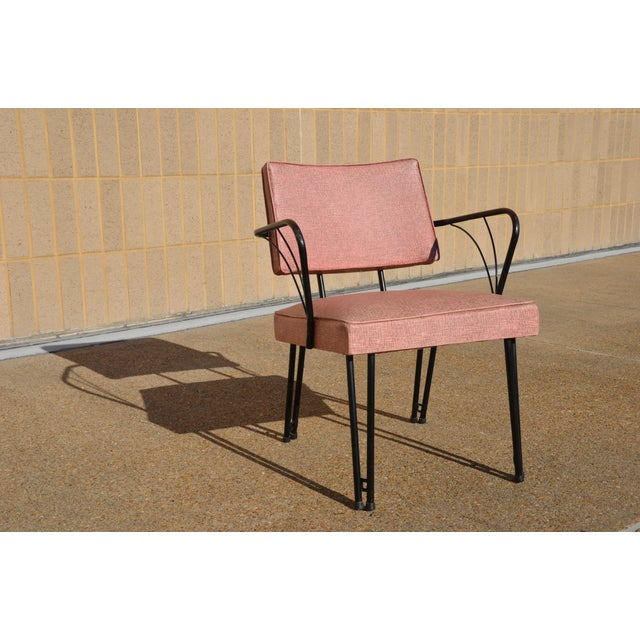 This Viko chair retains its original pink and gray naugahyde vinyl with black metal frame and legs. the arms are rubbed...