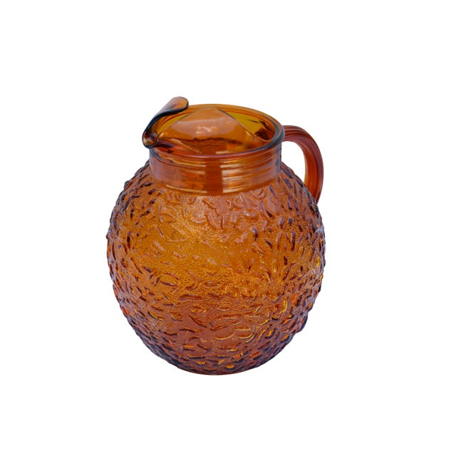 An amber colored glass pitcher made by Anchor Hocking. Made with a richly textured surface the pitcher has a folded...