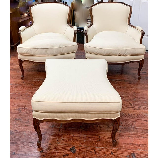 A pair of mid century French style arm chairs with a matching bow tie form ottoman. If the condition is not that is all...