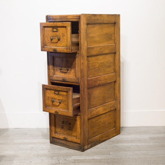 ABOUT An antique 4 drawer Oak file cabinet with brass pulls, brass label holders, brass key holes and dovetails joints....