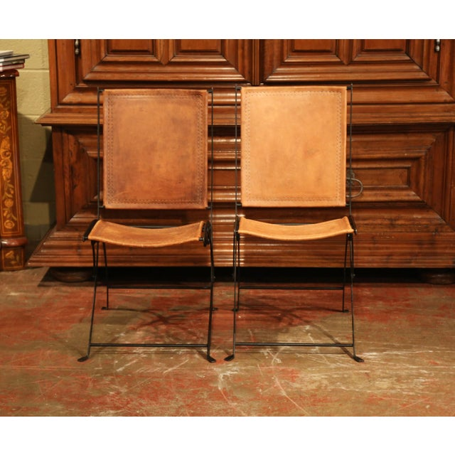 This pair of vintage chairs were found in Paris, France; crafted circa 1970, each folding chair is made of painted black...