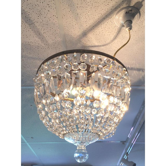 This beautiful chandelier features crystals in a variety of shapes to catch the light. At the center it has a floral...