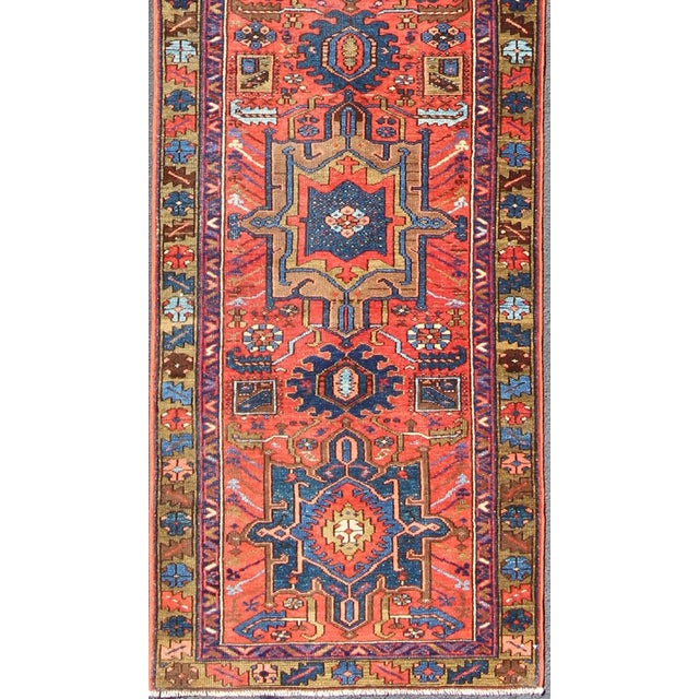This antique Karadjeh runner from 1920s is rendered in a geometric medallion design and colors such as blue, red, acid...
