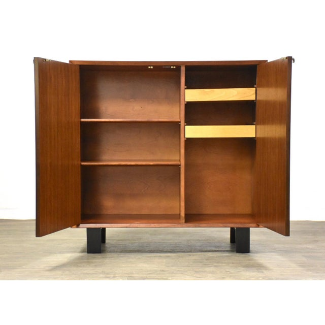A mid century modern walnut cabinet or credenza designed by George Nelson for Herman Miller with a black lacquered base...