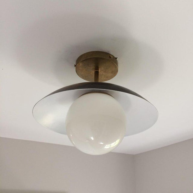 Custom-made solid brass and glass globe light fixture. We have left this brass with its natural patina, straight from the...