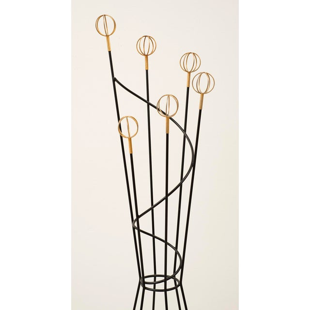 French modernist coat rack by Roger Feraud for Geo. In black lacquered metal with brass spherical finials. France, 1950s.