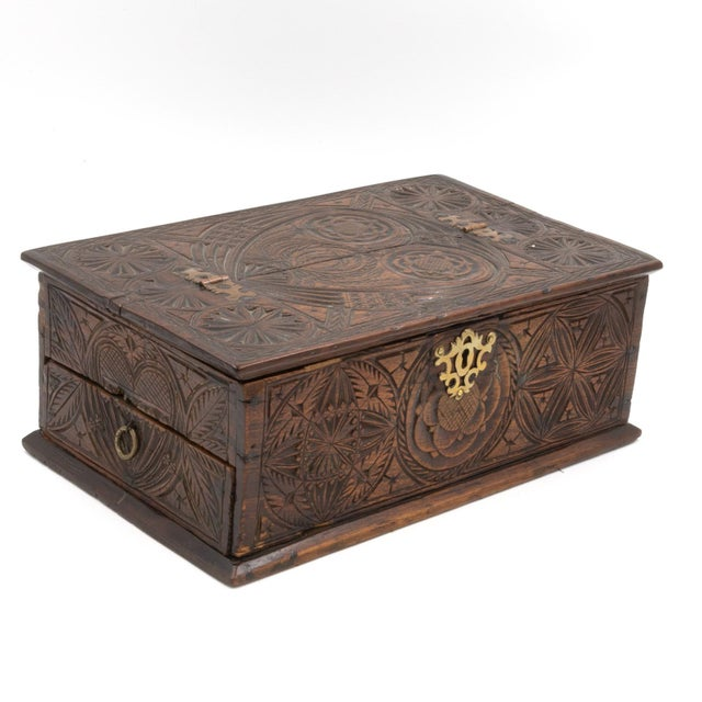 A 17th century carved oak box with side drawer dated 1655. Intricate carvings on all sides, including geometric figures...